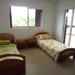 une chambre avec deux lits et un terrasse